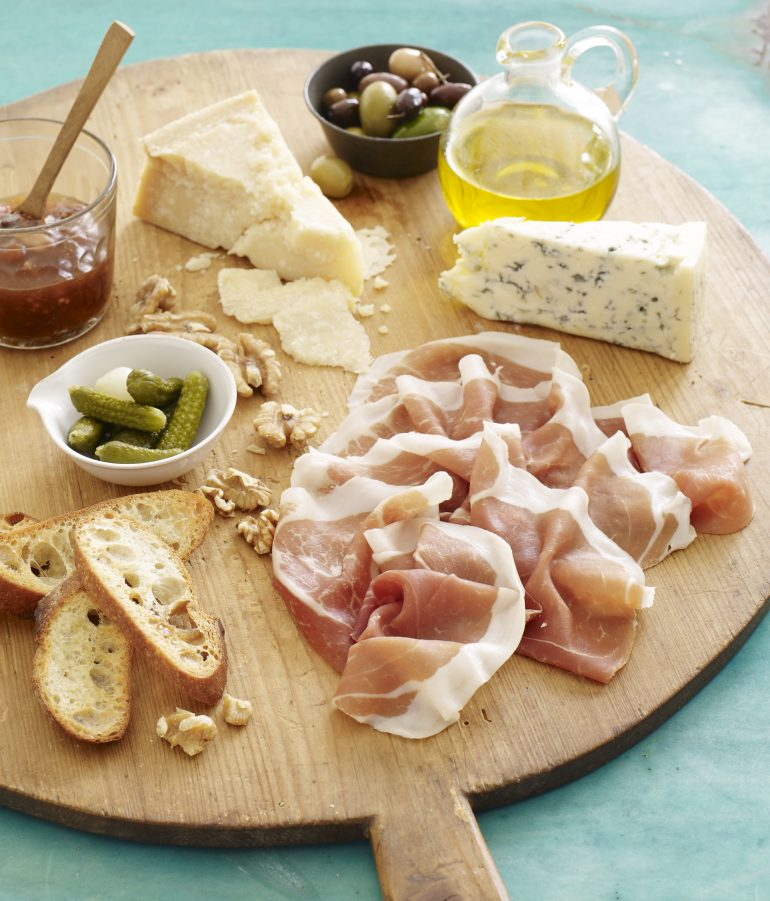 The classic charcuterie board with slices of Prosciutto di Parma, crostini, assorted cheeses, cured olives, petite pickles, olive oil and jam
