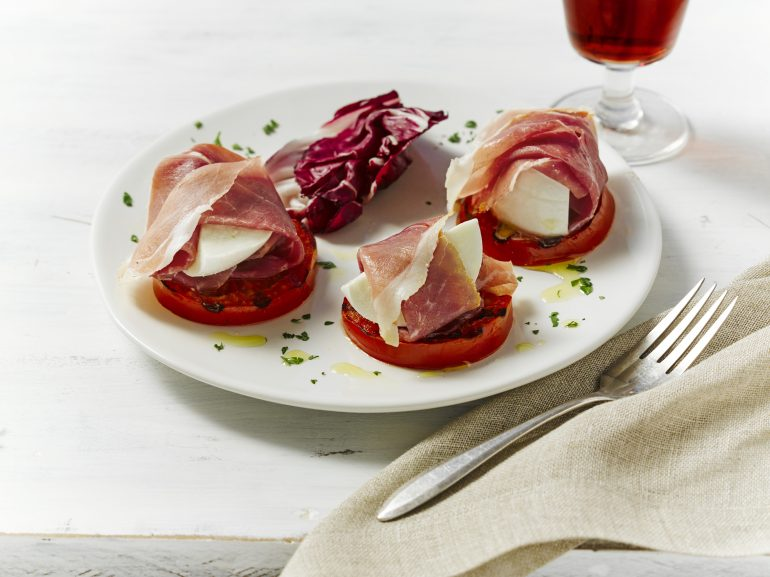 Slices of tomato topped with mozzarella, Prosciutto and a balsamic drizzle, served with a glass of Fino Sherry