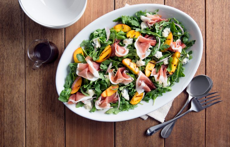 Arugula salad with grilled oranges, Parmesan cheese and slices of prosciutto served with fig jam dressing on the side