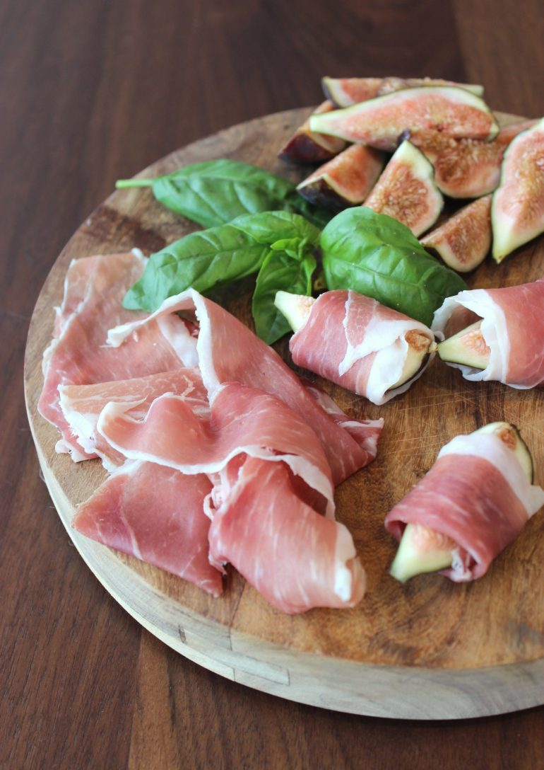Sweet figs wrapped in slices of prosciutto displayed on a charcuterie board