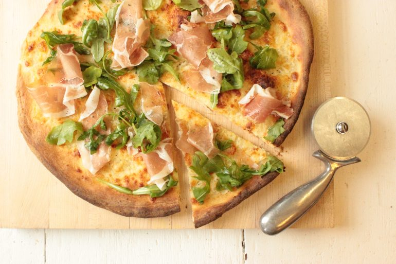 Savory Prosciutto-Topped Pizza with peppery arugula on a cutting board ready to serve