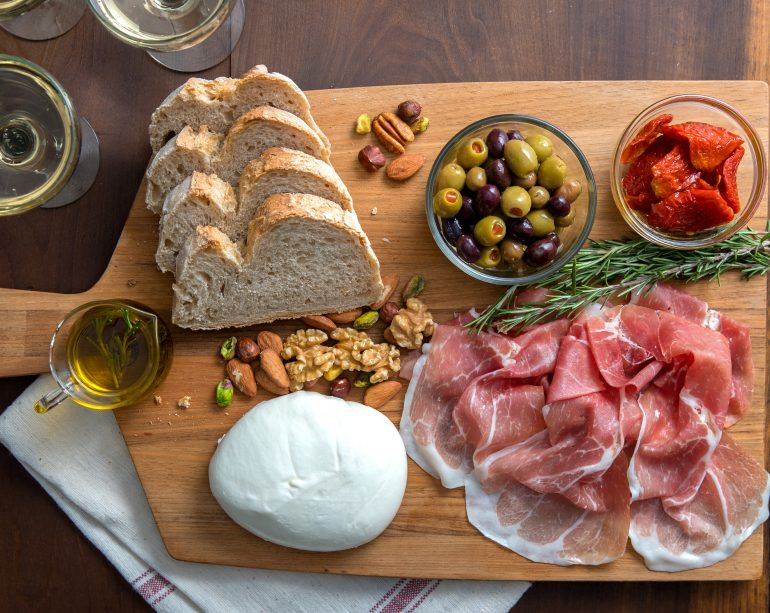 The classic charcuterie board with slices of Prosciutto di Parma, roasted red pepper, assorted nuts, burrata cheese, cured olives, and olive oil