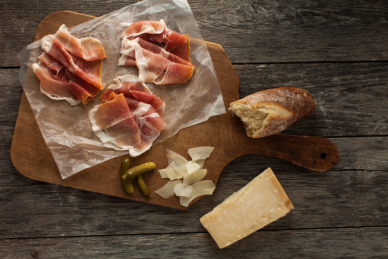 The perfect charcuterie board with slices of Prosciutto di Parma, shaved parmesan cheese, petite pickles and a baguette.