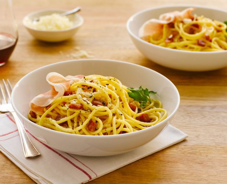 Spaghetti Carbonara with Prosciutto in a white bowl, ready to eat