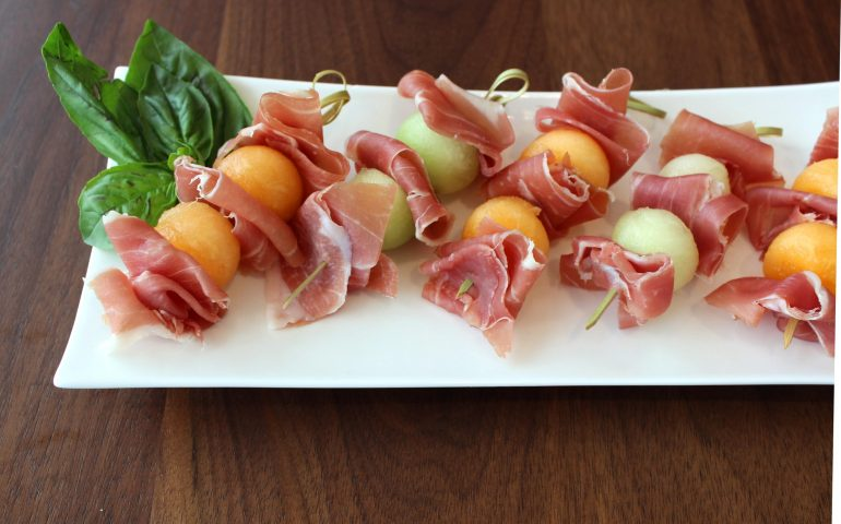 Prosciutto between cantaloupe and honeydew melon secured with toothpicks on an appetizer plate