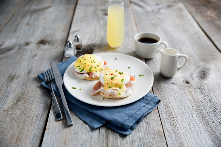 Prosciutto topped eggs benedict served with coffee and champagne
